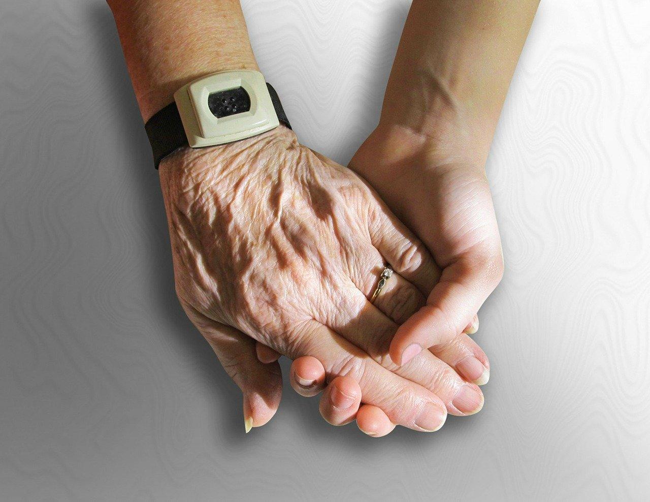 Hände von Pflegebedürftigem und Pfleger